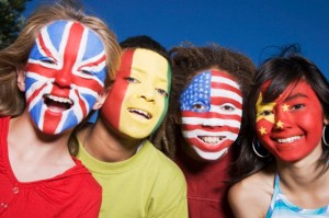 Children with United Kingdom, Guinean, United States and Chinese flags painted on faces